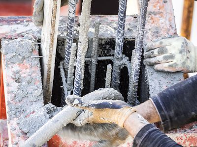 High angle view of a construction worker working at a construction site, with a hose at the hands being work with the concrete