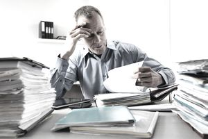 A businessman working at a desk with stacks of paperwork and binders