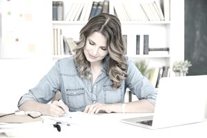 Woman working on paperwork at a desk in front of a white laptop