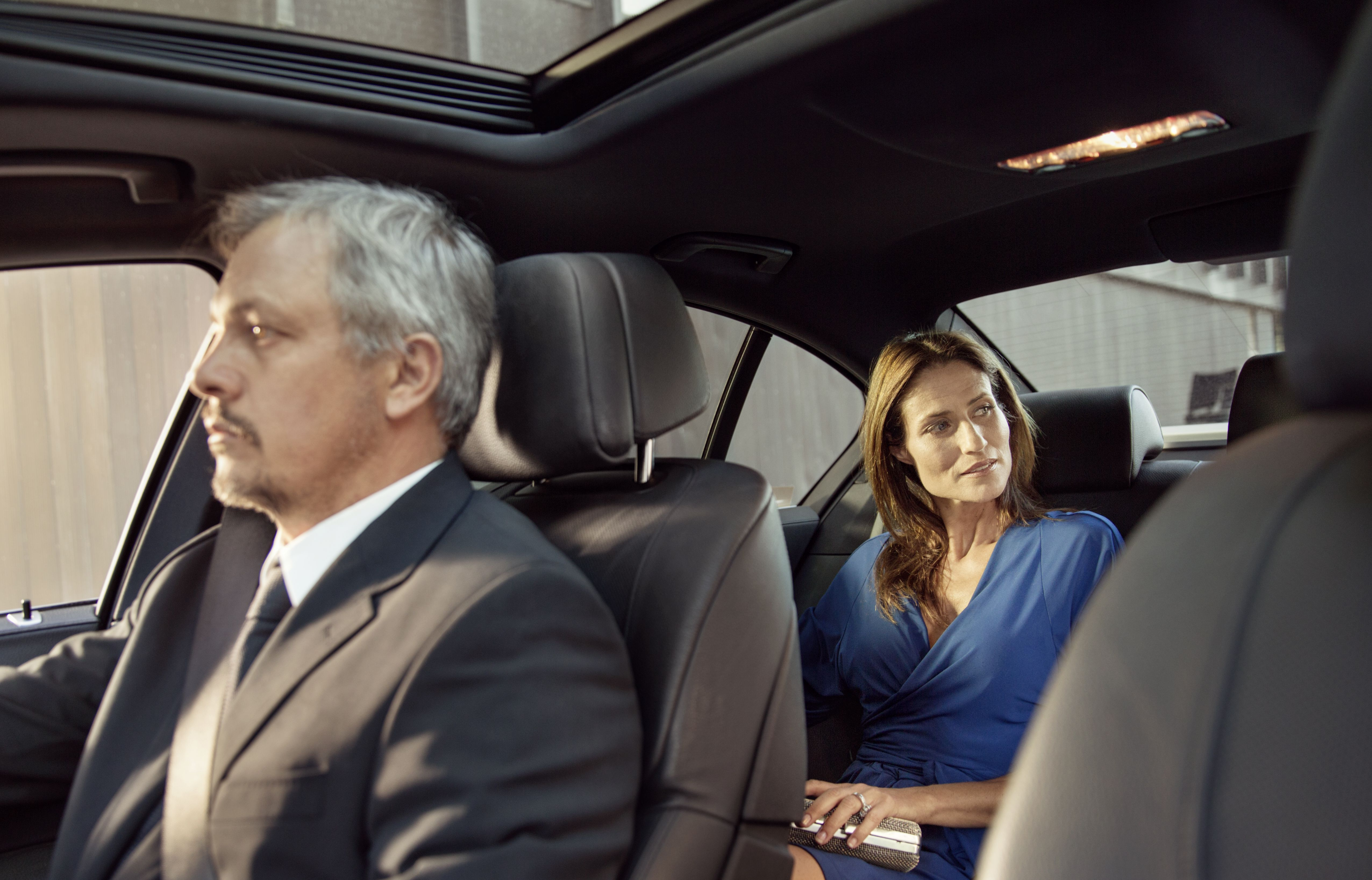 Chauffeur is driving mature woman.