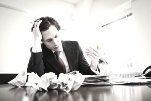 a business man sitting at a desk with crumpled pieces of paper