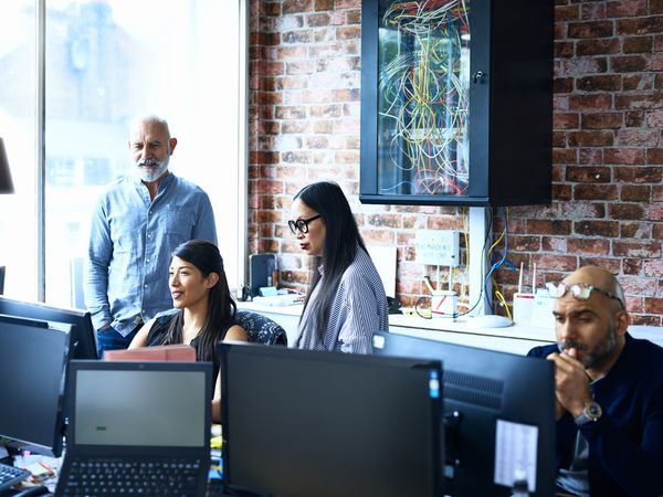 diverse group of employees looking at a computer screen in an office with a lot of computers and technology