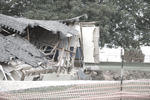 Building with extreme damaged caused by a sinkhole that is slowly eating the structure.