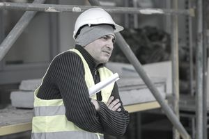 Engineer In Reflective Clothing With Arms Crossed Standing At Construction Site