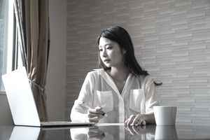 Woman seated at a home table with a laptop, documents, and coffee mug