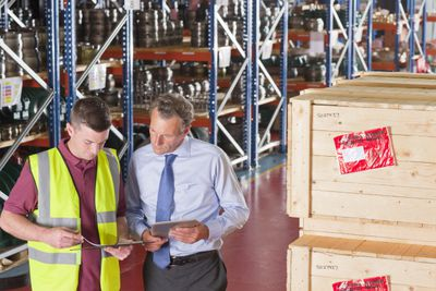 Businessman and worker with digital tablet and paperwork in warehouse