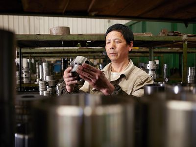 Worker inspecting metal parts in hydraulics factory
