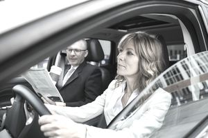 A woman taking a test drive with a salesman.
