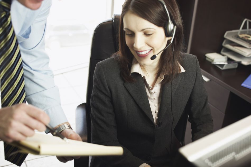 A woman with a headset looking over a man's notes