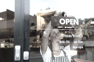 A small business owner turns the Open sign to