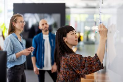 Young businesswoman writes on whiteboard as two colleagues watch