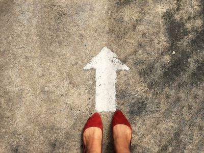 Woman's feet in red flats standing over an arrow pointing forward/up