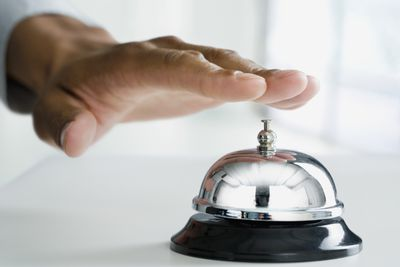Close-up of a customer's hand about to ring counter service bell