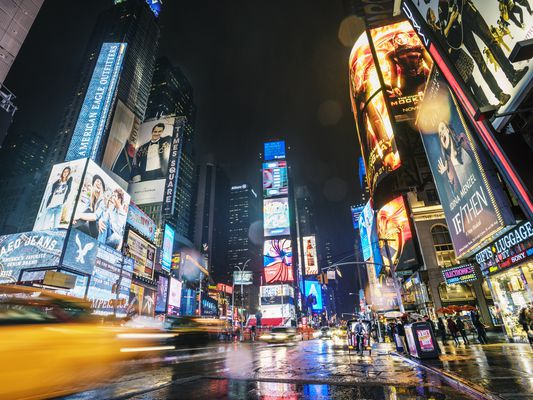 View of neon signs and traffic in Times Square at night, New York, USA