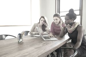 Three young female entrepreneurs discuss plans with a laptop