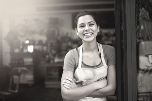 Happy woman standing in a doorway wearing an apron