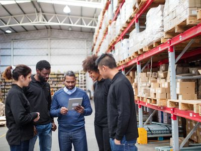 Warehouse manager discussing with logistics team