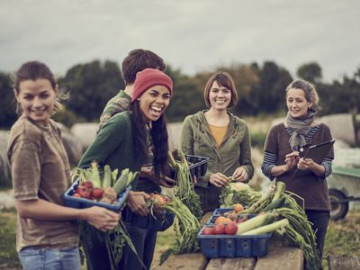 Five young people outside at a table covered with fresh produce.
