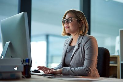 Woman Wearing Glasses in an Office, Staring Into a Desktop Computer Screen While Typing on Keyboard