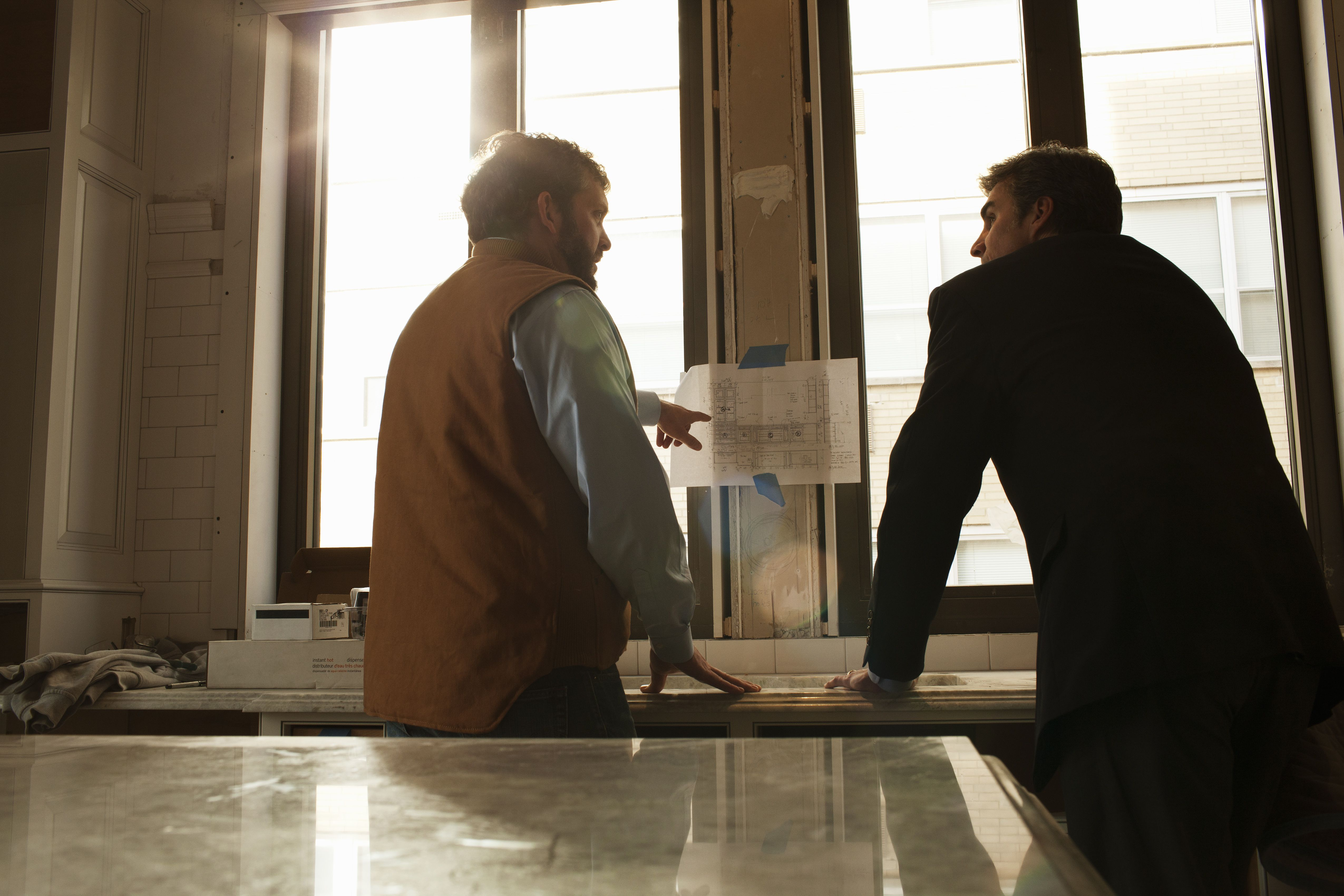 A builder pointing at a diagram and talking to business owner about modification to a rental space.