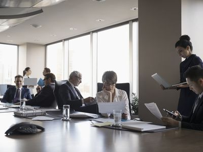 Lawyers reviewing paperwork and using laptops and digital tablet in conference room