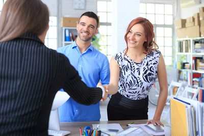 Small business owners shaking hands with a consultant who will need to see their business requirements document.
