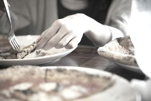 Woman's hand holding a piece of pizza and using a fork to move the pizza piece