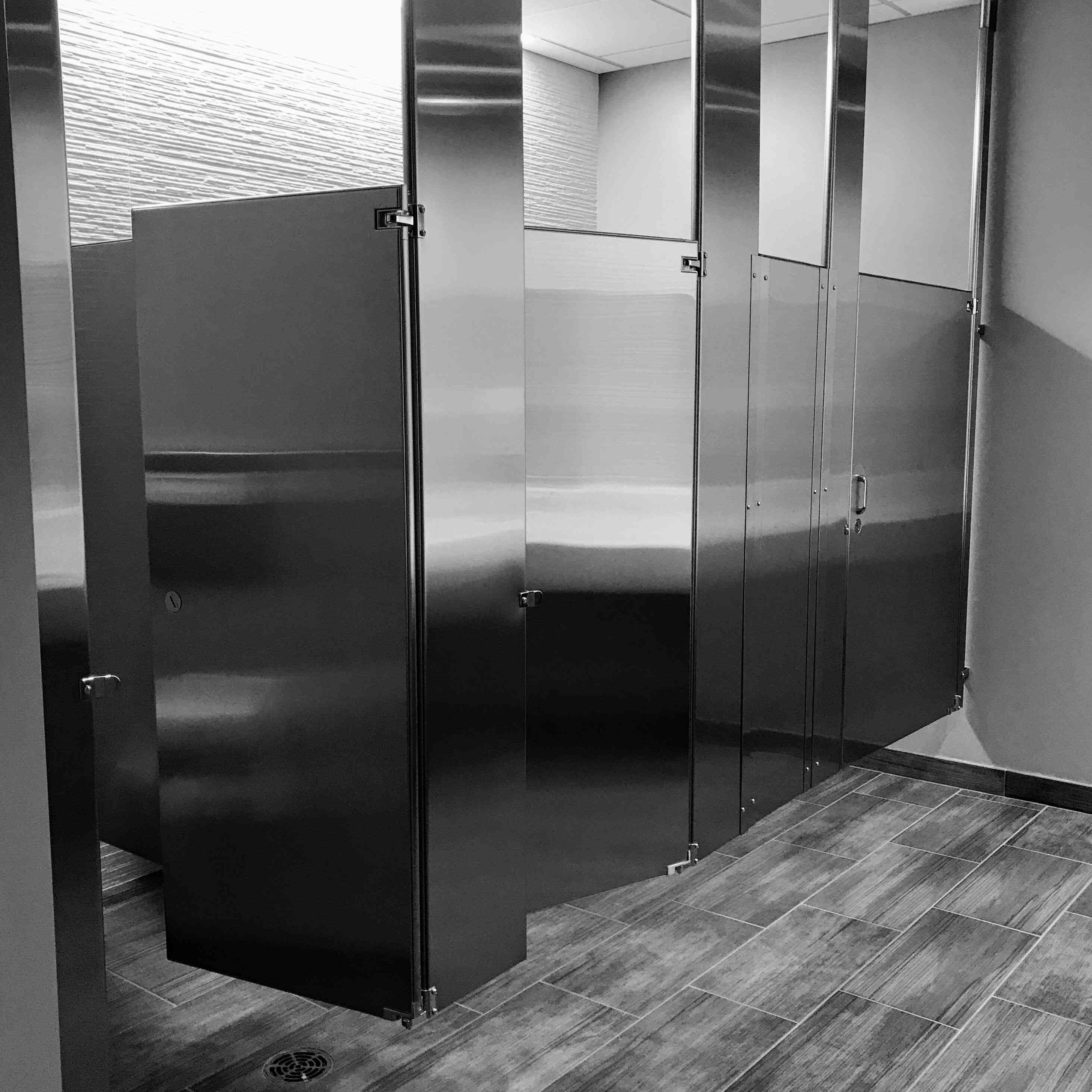 Interior of bathroom with metal stall partitions.