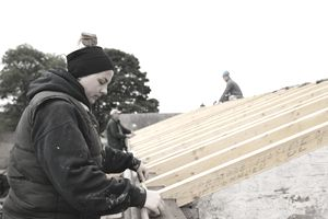 Female construction worker framing rafters during the winter wearing layers of clothing to stay warm.