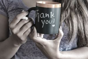 Woman holding a coffee mug with thank you written on it in chalk.