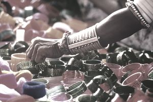 Image is of a Indian person's forearm selecting a bracelet from a display of bracelets for sale.