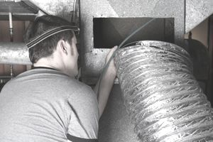 Worker in an attic space conducting an air duct cleaning.