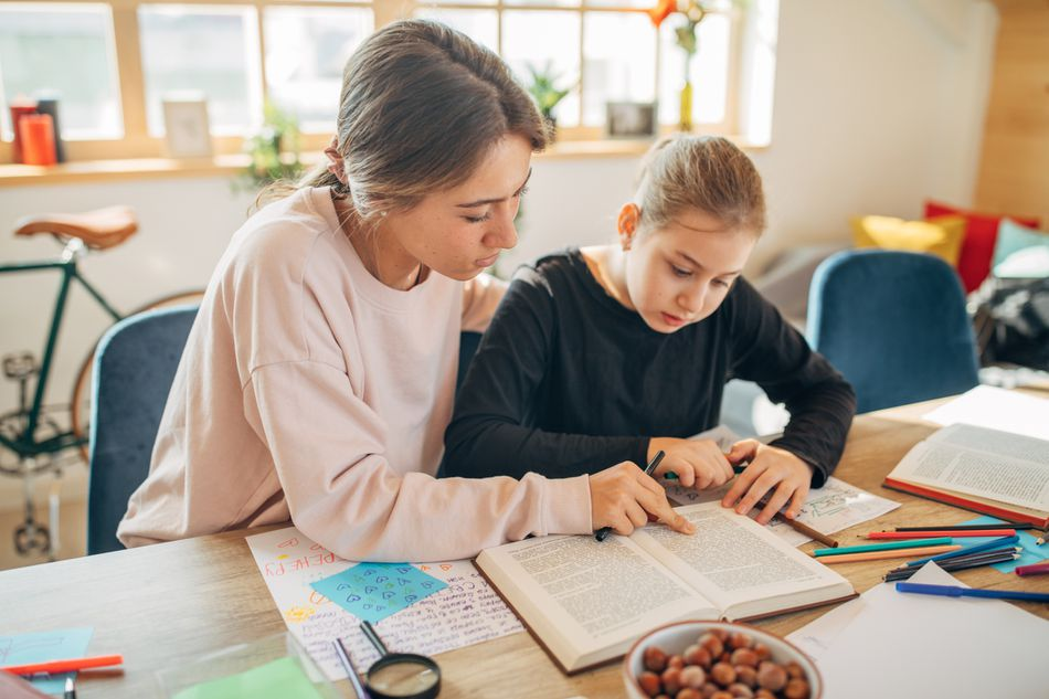 Teen Working as a tutor with a young child