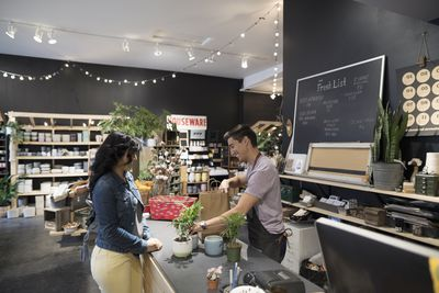 Male shop owner helping female customer buying plants at shop counter