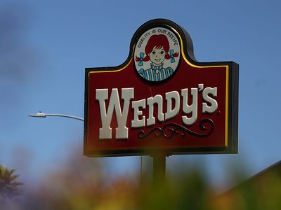 A sign is posted in front of a Wendy's restaurant