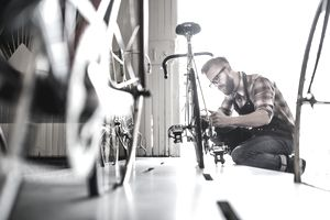 A man working in his sole proprietorship bicycle repair shop