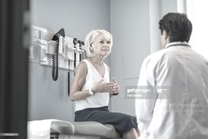 Older woman sitting on an exam table talking to doctor