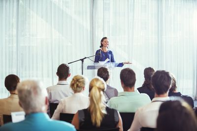 Young businesswoman opening a conference with a plenary session