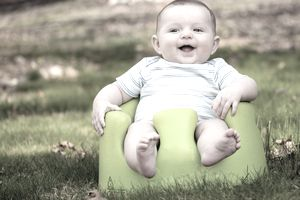 Happy baby using training Bumbo seat to sit up