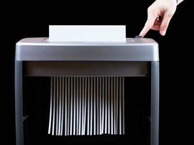 Hand operating paper shredder to recycle paper