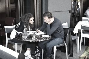 Young couple seated at bistro table both looking at his phone