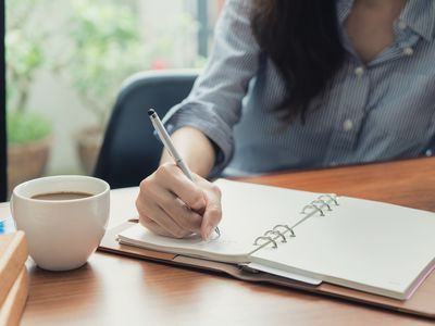 Close-up of woman writing in notebook while sitting in chair in front of window at cafe.