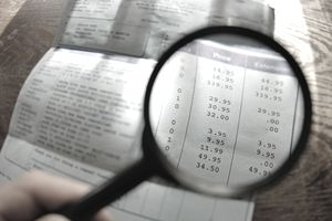 Man holding magnifying glass over invoice, close up of invoice