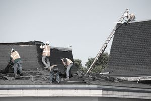 Workers removing asphalt shingles from a roof to be recycled.