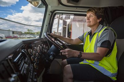 A woman drives a commercial truck onto a job site.
