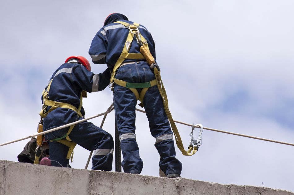 Construction workers wearing safety harnesses on multi-level construction site
