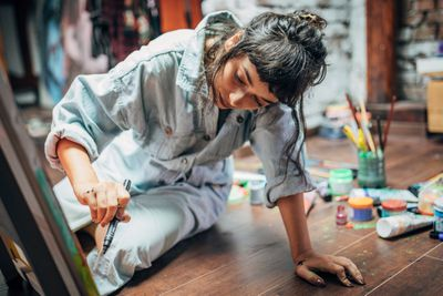 Woman painting on the floor at home