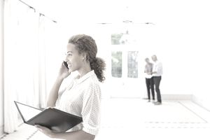 Real estate buyer agent talking on a cell phone inside a house she is showing to a couple standing in the background.