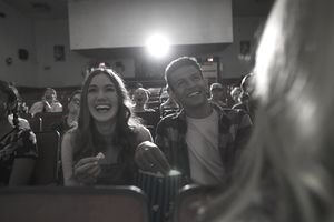 Laughing tween couple eating popcorn, watching movie in movie theater
