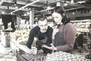 business owners discuss in grocery store with tablet
